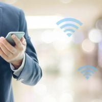 Man in a business suit using his mobile device to access Wi-Fi