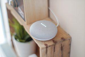 Round Google Home Alexa speaker on a wooden bookshelf