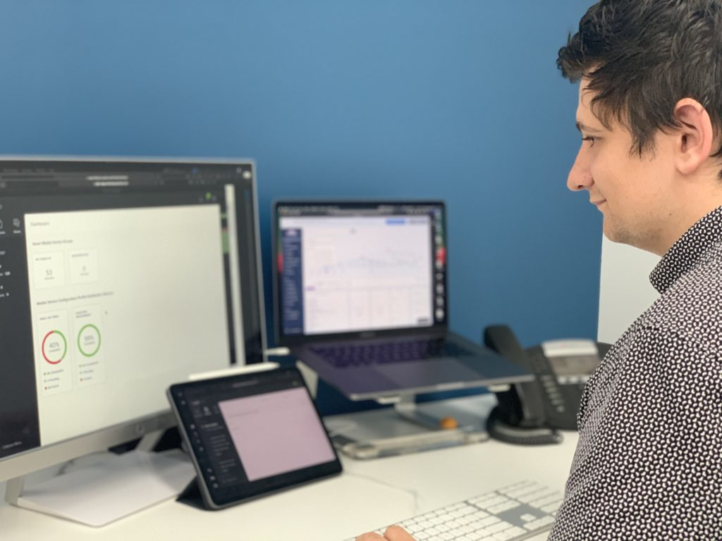 A SupportMyMac employee sitting at his desk at work, looking at two computer screens and an iPad, monitoring the Mobile Device Management (MDM) solution