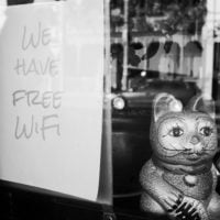 """Black and white photo of a storefront with a sign in the window that says """"we have free WiFi"""" and a Chinese lucky cat statue beside it"""