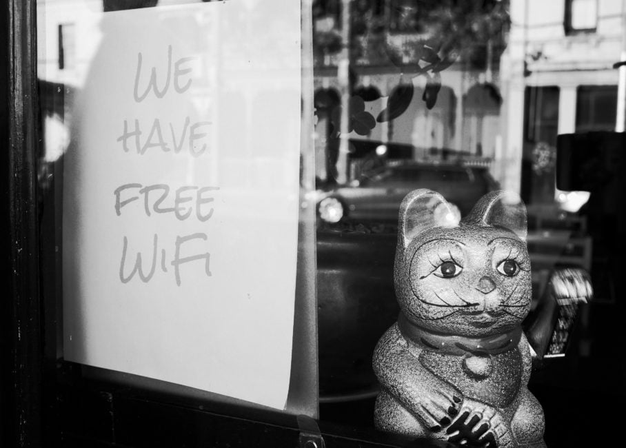 "Black and white photo of a storefront with a sign in the window that says ""we have free WiFi"" and a Chinese lucky cat statue beside it"