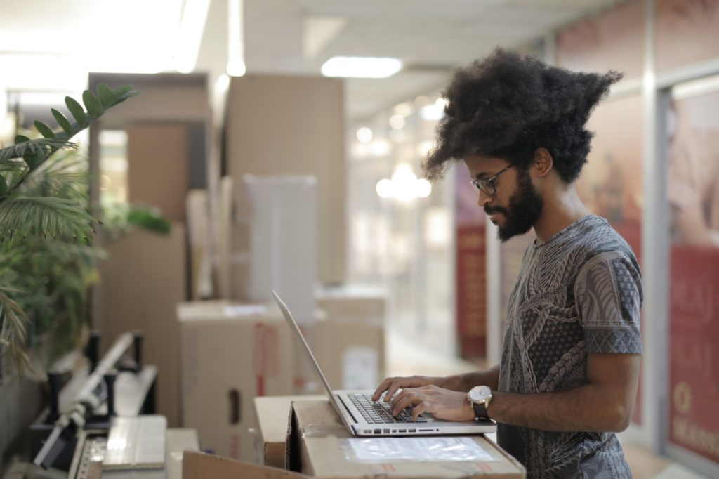 Focused black man working on a laptop in an office space, surrounded by cardboard boxes