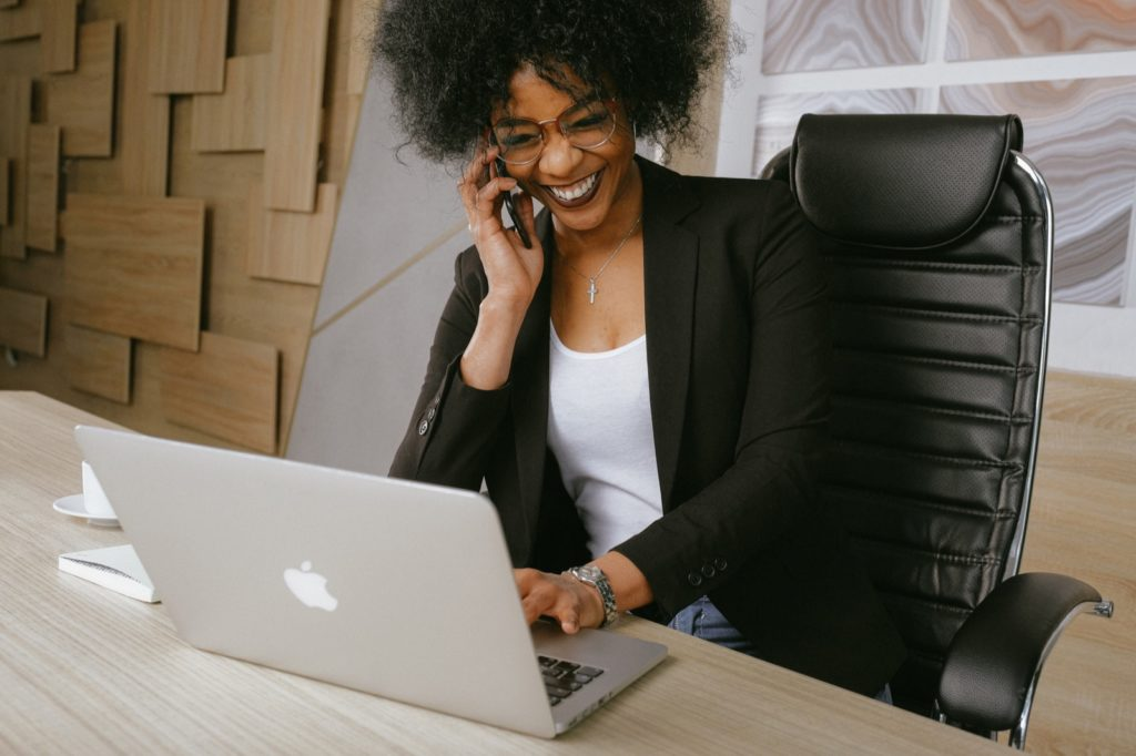 Smiling, ethnic woman in a black blazer sitting on black office chair looking at her Apple computer while talking on her iPhone