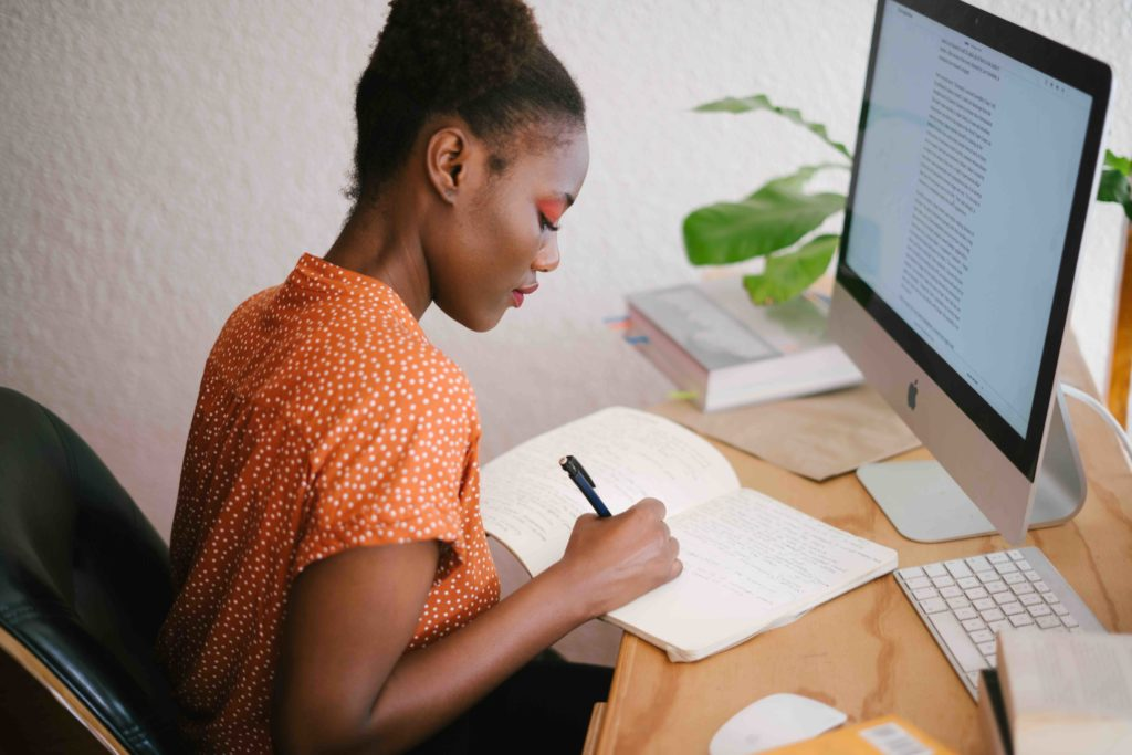 Woman in orange shirt working at her desk, in front of a computer