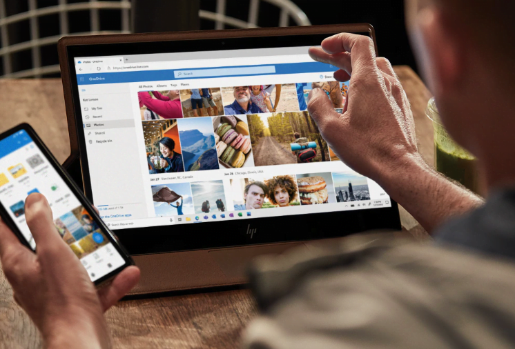 Person using Microsoft OneDrive on tablet and phone