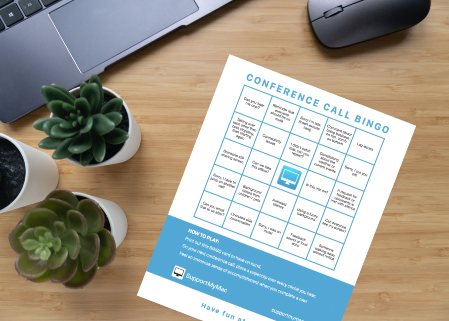 SupportMyMac's Conference Call Bingo card sitting on a wooden desk, in front of a laptop