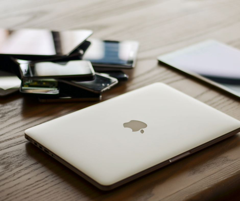 A pile of Apple devices sitting on a wooden table, including laptop, iPads and iPhones, for IT asset management
