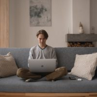 Young man sitting cross-legged on a living room couch, working on his laptop