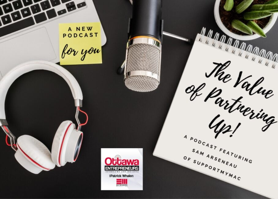 "Birds eye view of a black desk, with an Apple laptop, headphones, and a notebook on it. The notebook says ""The Value of Partnering Up!"" Ottawa Entrepreneurs Podcast Sam Arseneau on it."