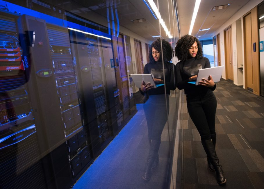 Ethnic woman in a small business office holding a laptop. She's standing in front of a glass wall with servers behind it that are storing back ups.